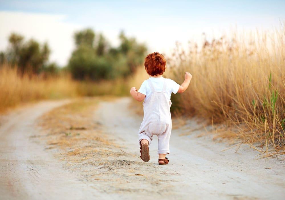 Kleinkind läuft durch Wiese